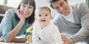 Smiling man and woman with baby on carpet