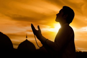 Silhouette of asian muslim man raising hand and praying during sunset background