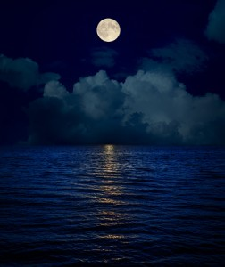 full moon over clouds and dark water with reflections
